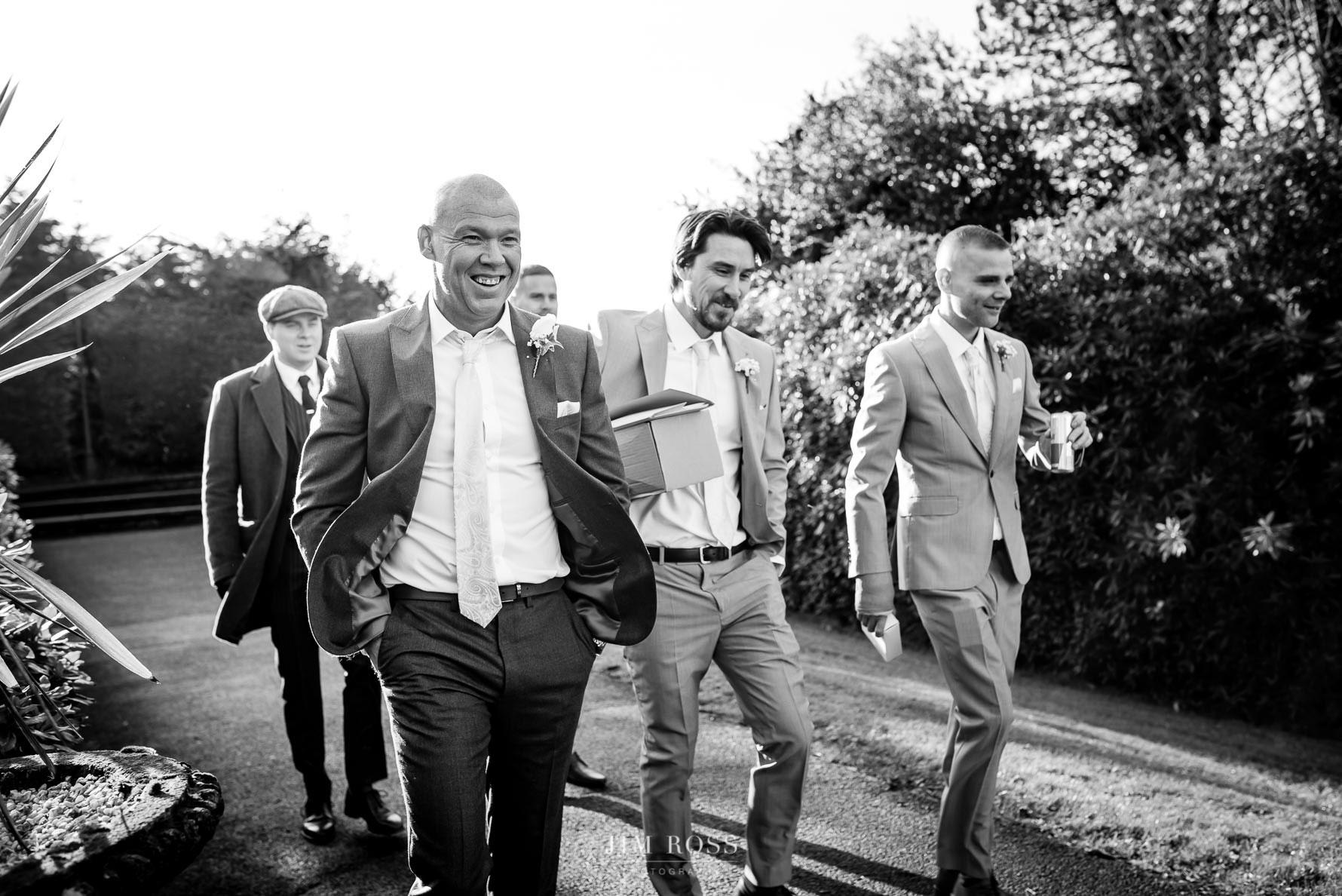 Groomsmen walk to church in Bowness