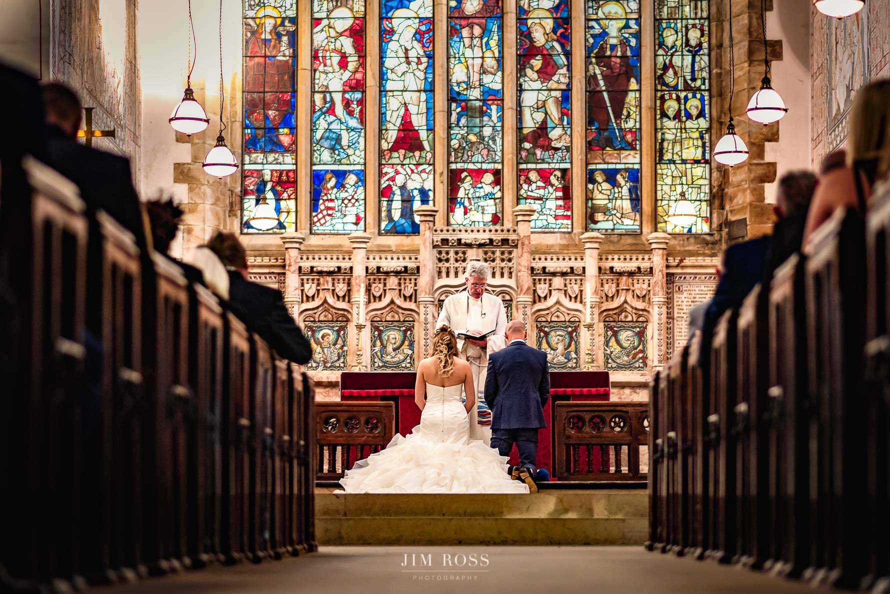 Couple kneeling for vows in church