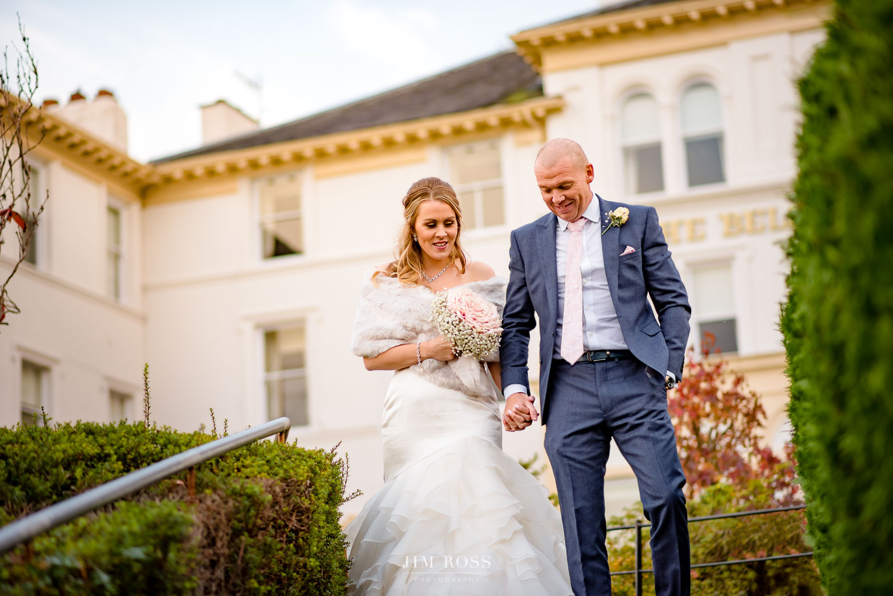 Bride and groom walk from Belsfield Hotel