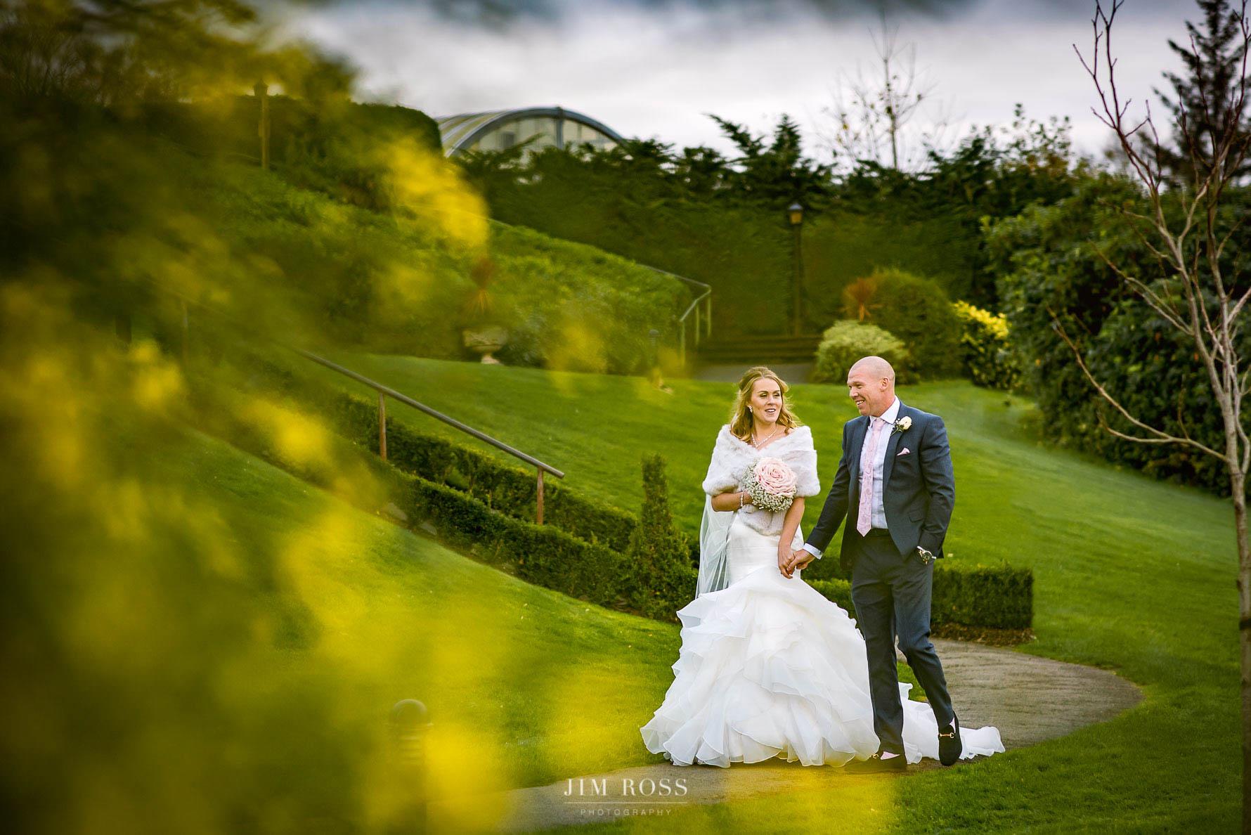 Couple walk through Belsfield Hotel gardens