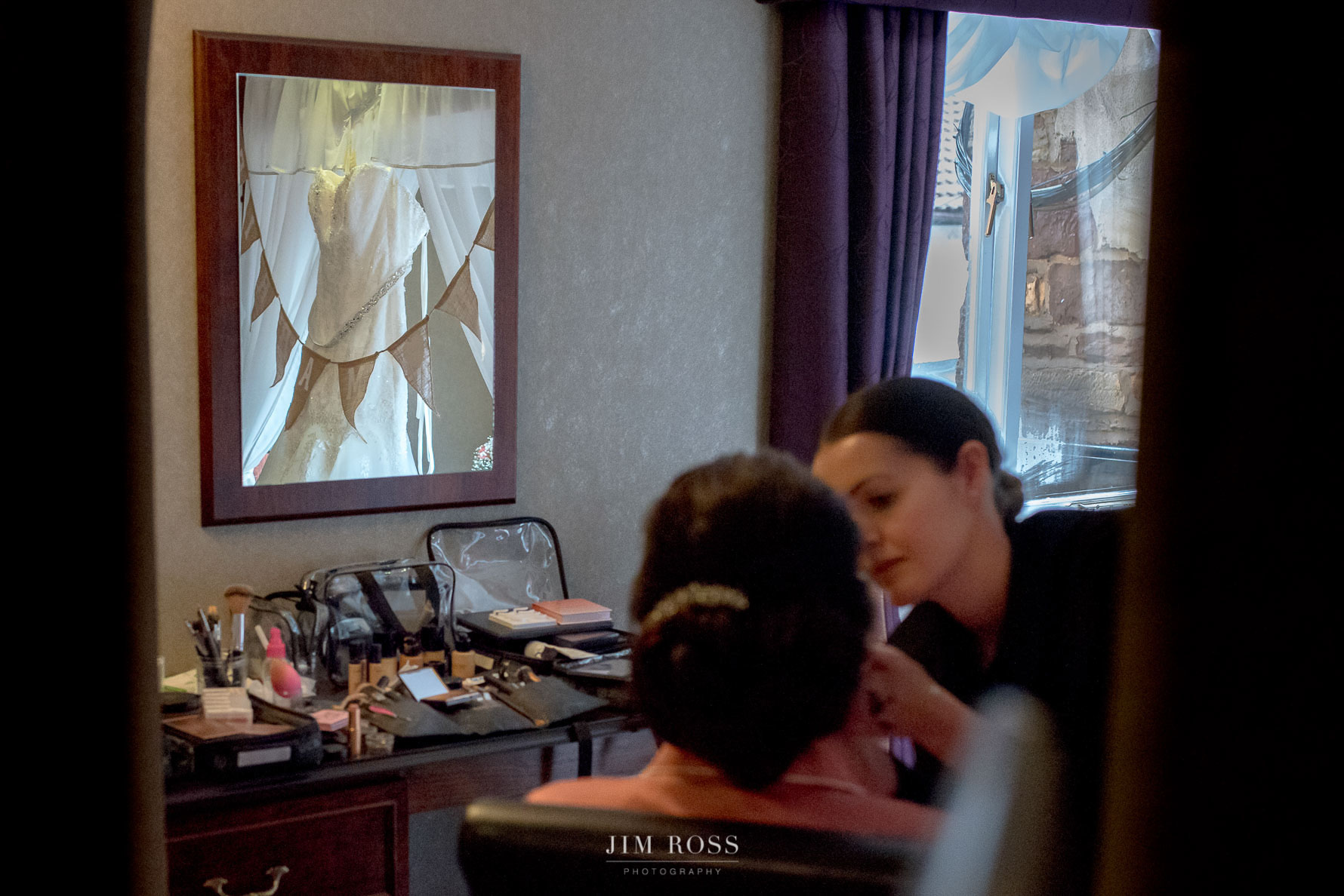 Makeup artist at work with dress hanging in mirror