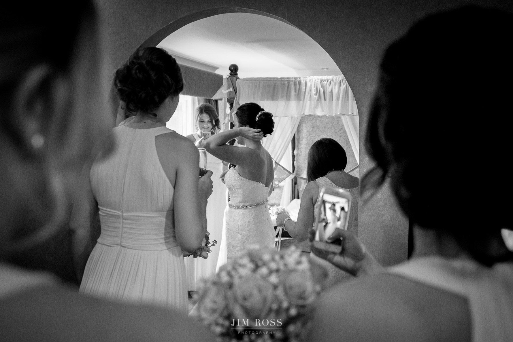 Bridesmaids gather to check bride's hair