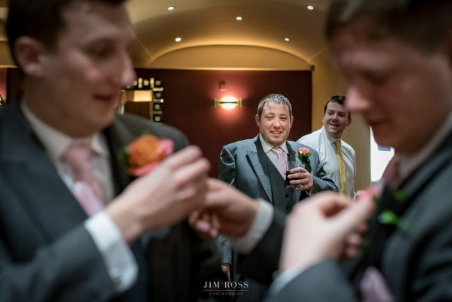 Groomsmen check button hole flowers in hotel