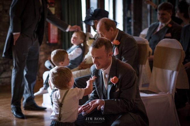 Groom playing with children while waiting for bride