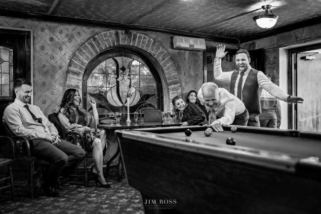 Groomsmen fun around pool table