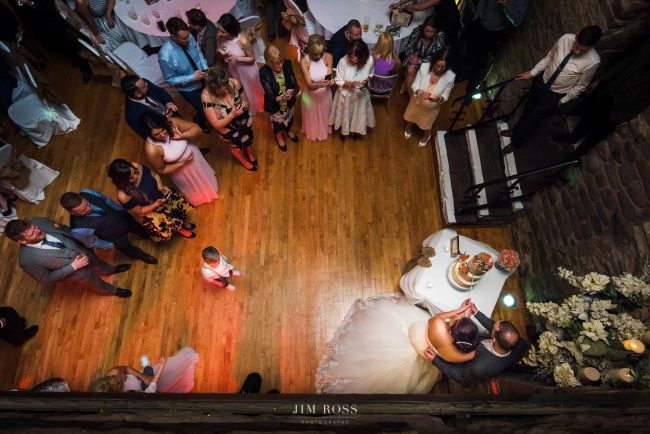 Cutting the wedding cake in medieval banquet hall