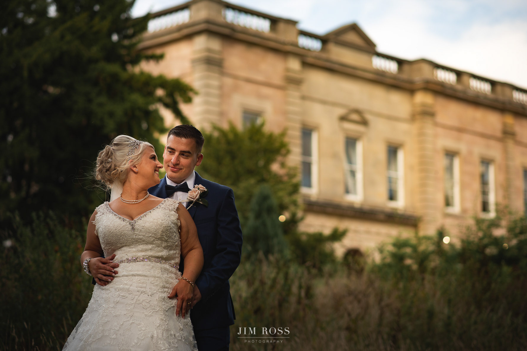 Couple portrait with grand manor house in background
