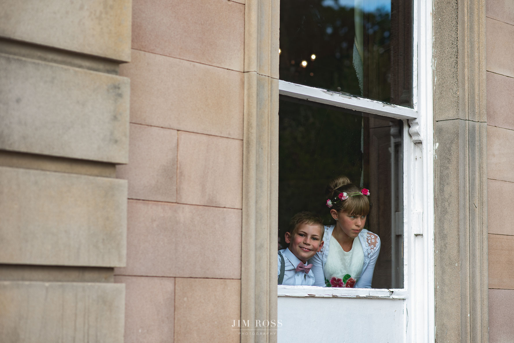 Children peek at wedding guests through window