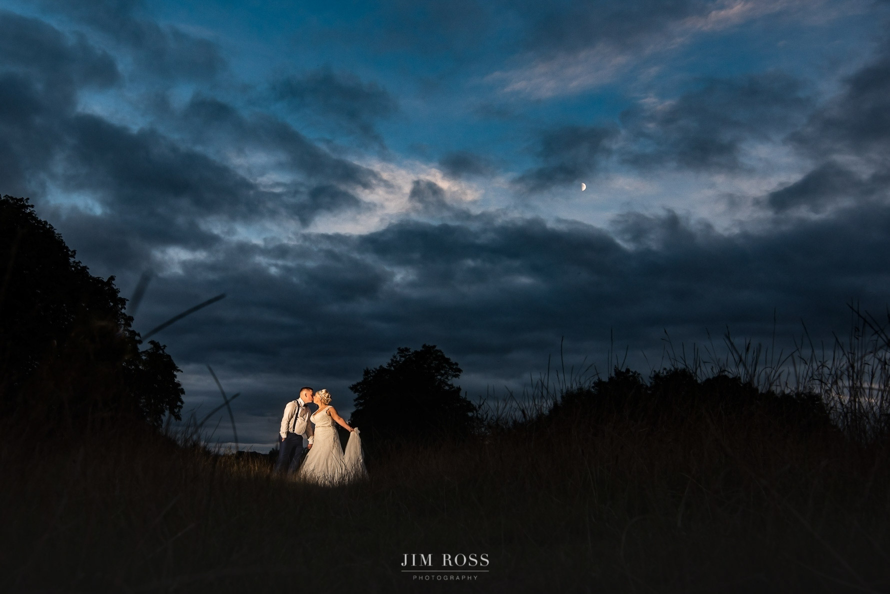 Night portrait of couple with dramatic sky