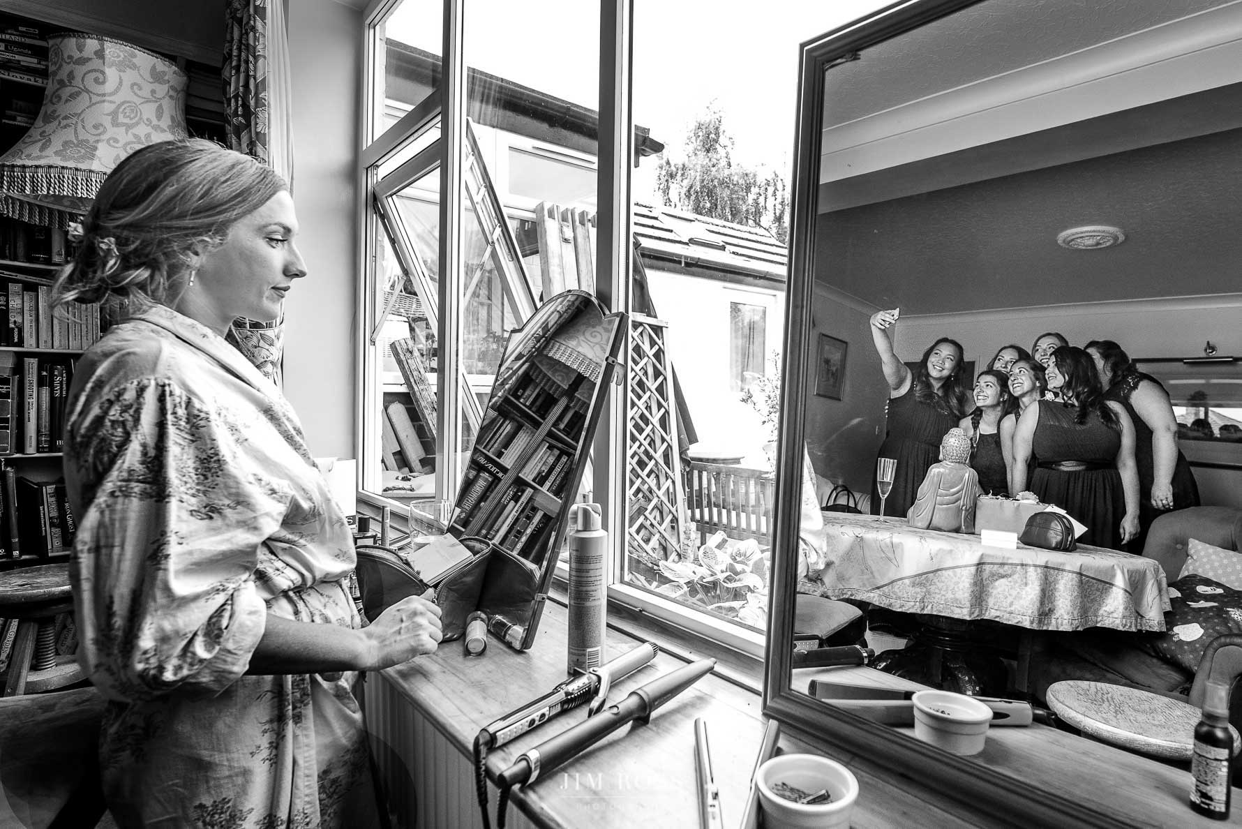 Bridesmaids ready in mirror while bride does makeup