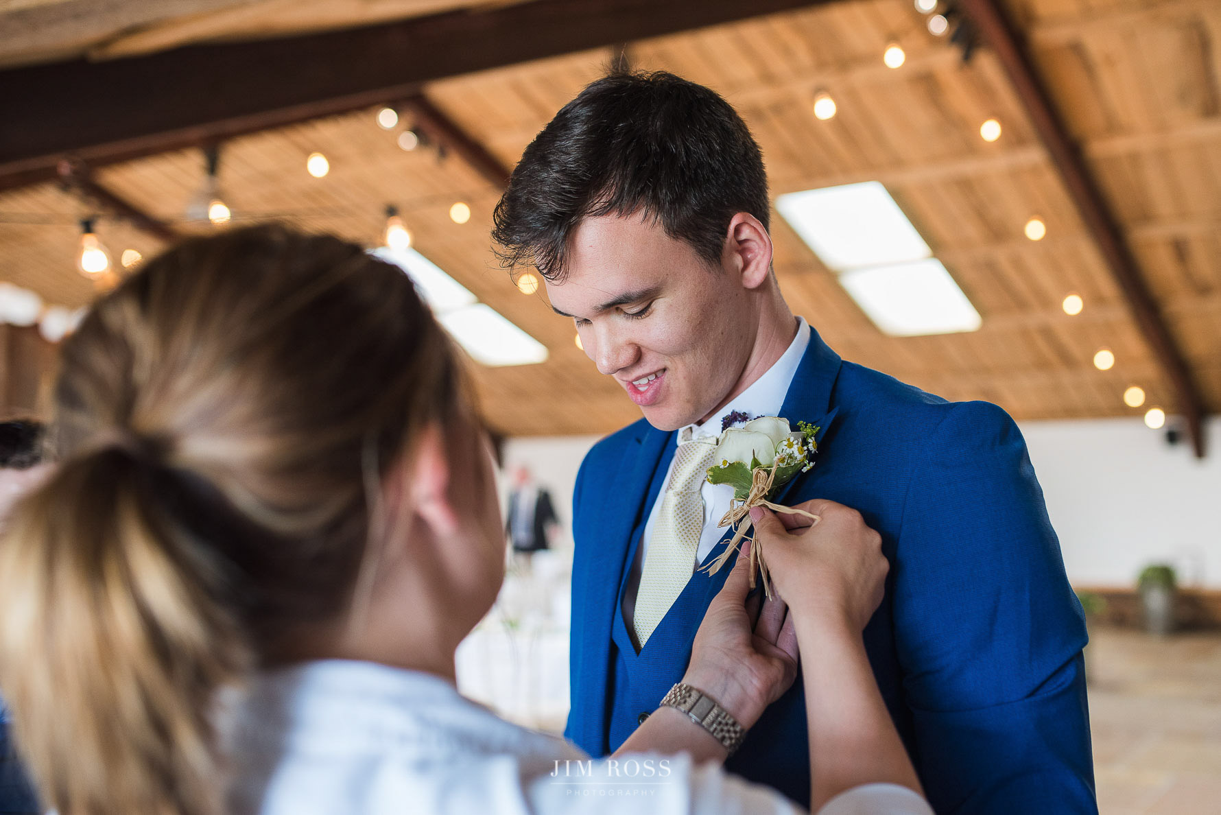 Groom gets help with button hole