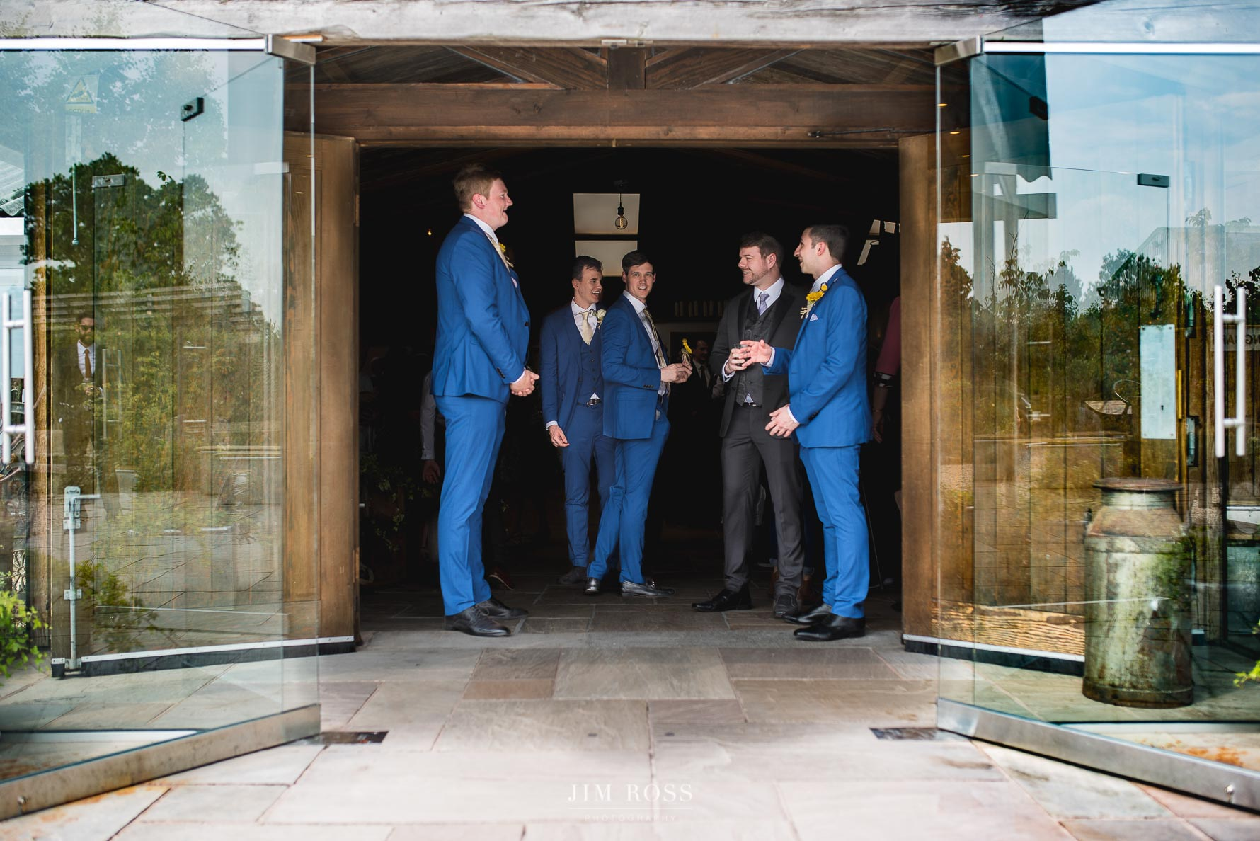 Groomsmen stand in wait at Owen House Wedding Barn