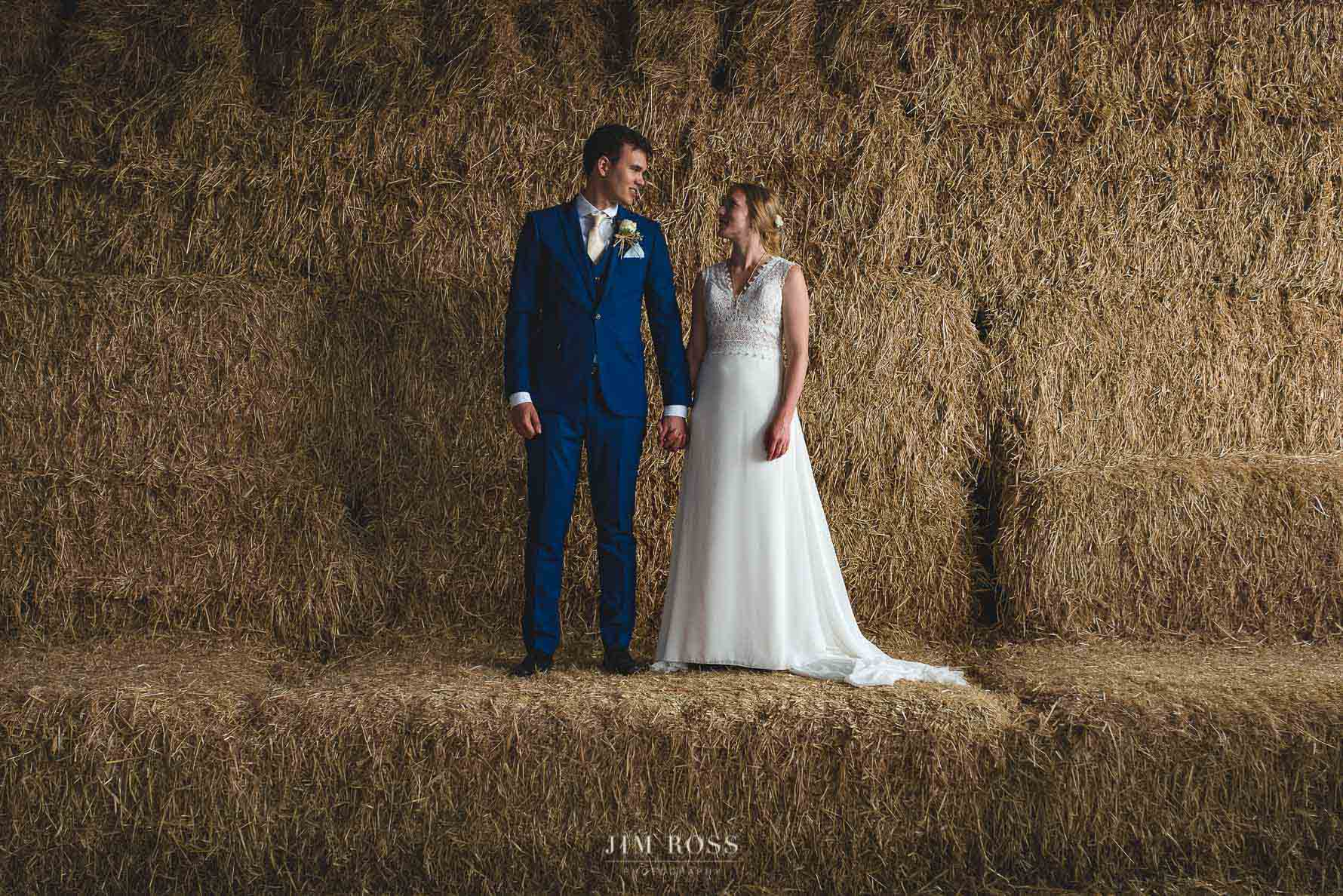 Newlyweds standing on hay bales