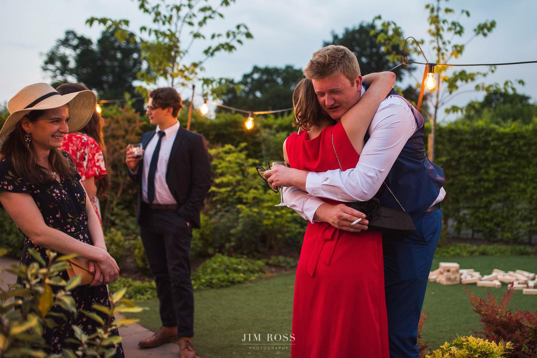 Hugs for the groomsman in wedding barn garden
