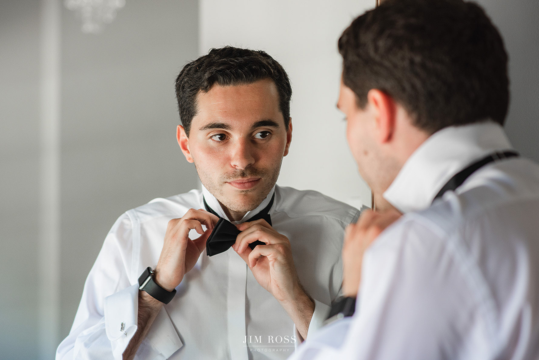 Groom adjusts bow tie