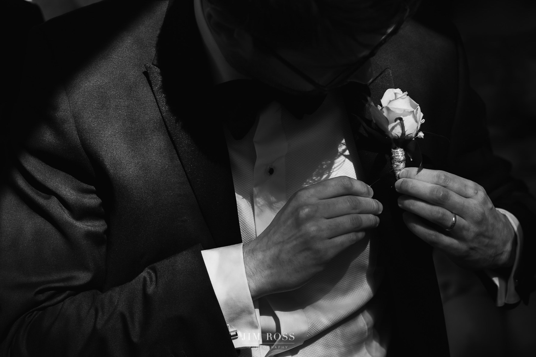 Groomsman adjusts button hole flower