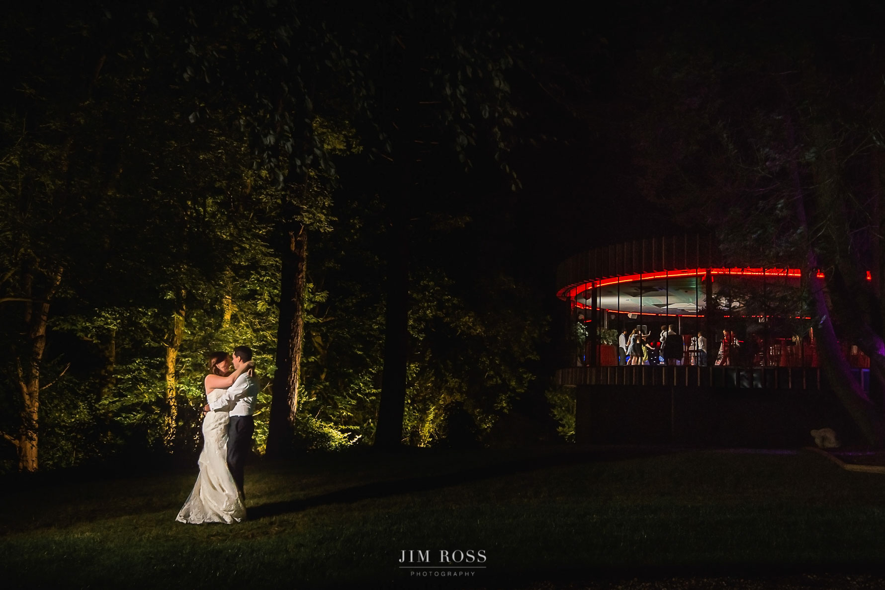 Night time couple portrait in garden as guests party in background