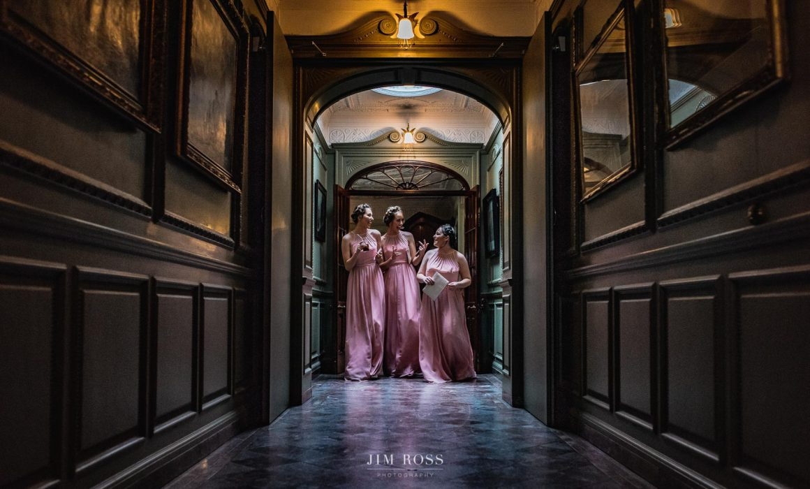 Bridesmaids in panelled corridor Thornton Manor