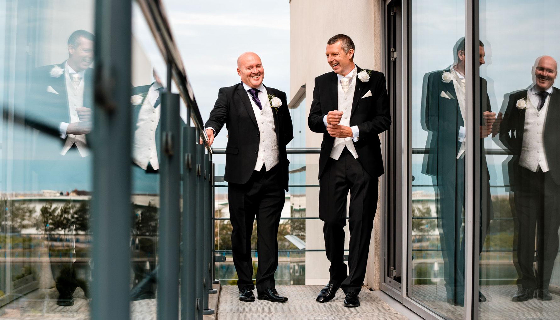Groomsmen on hotel balcony