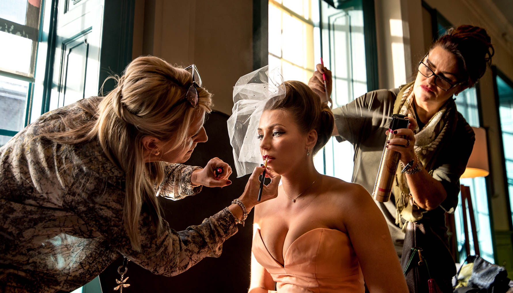 Bride getting pampered by make-up and hair artists
