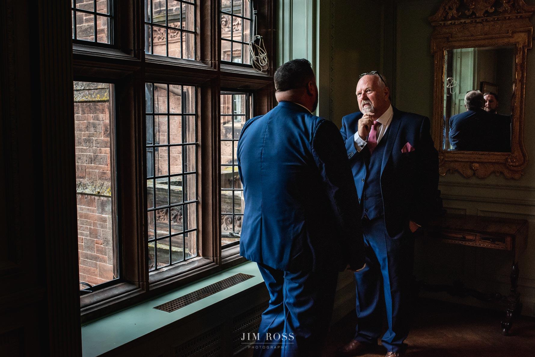 Groomsmen wait in grand manor