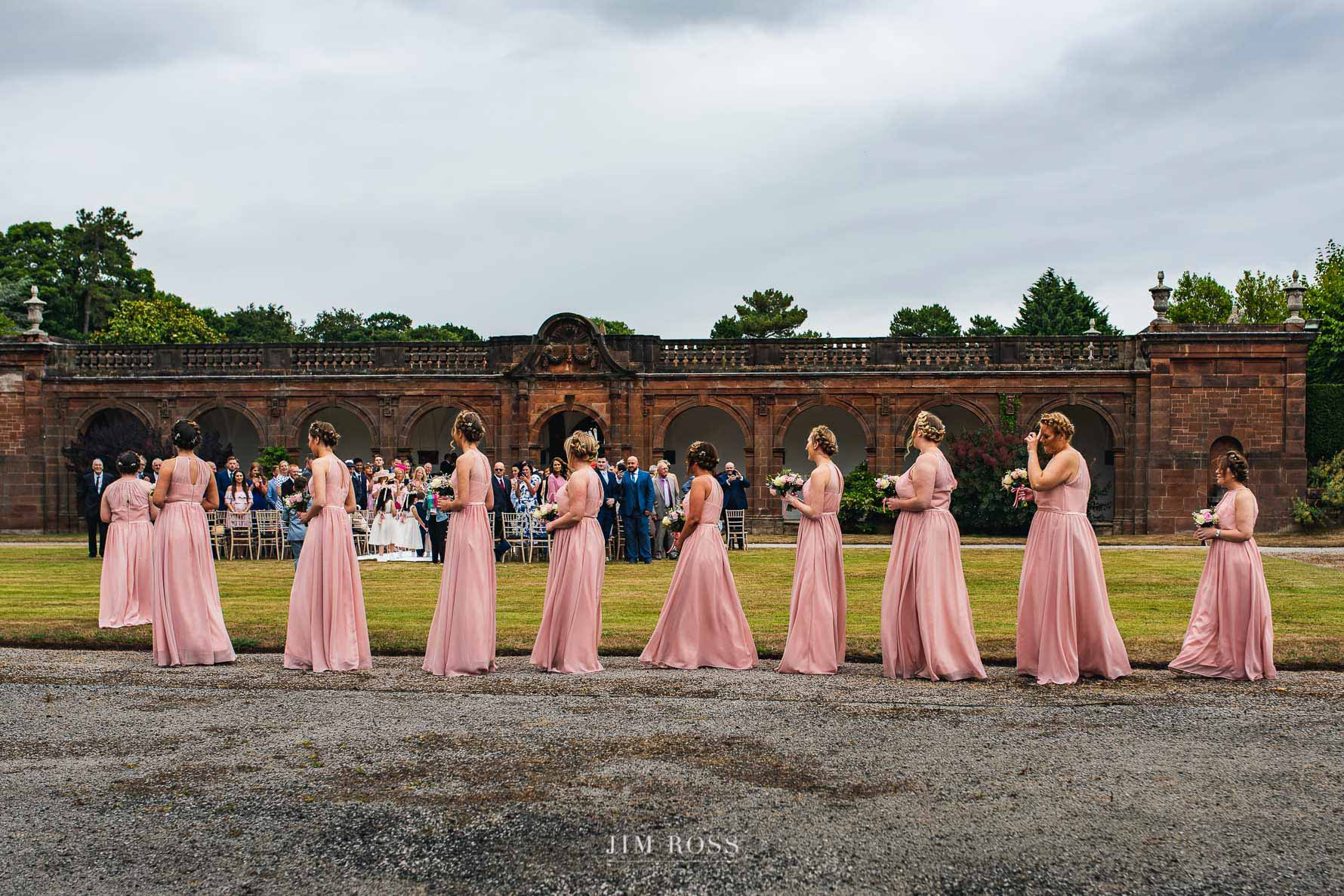 A line-up of bridesmaids at outdoor ceremony