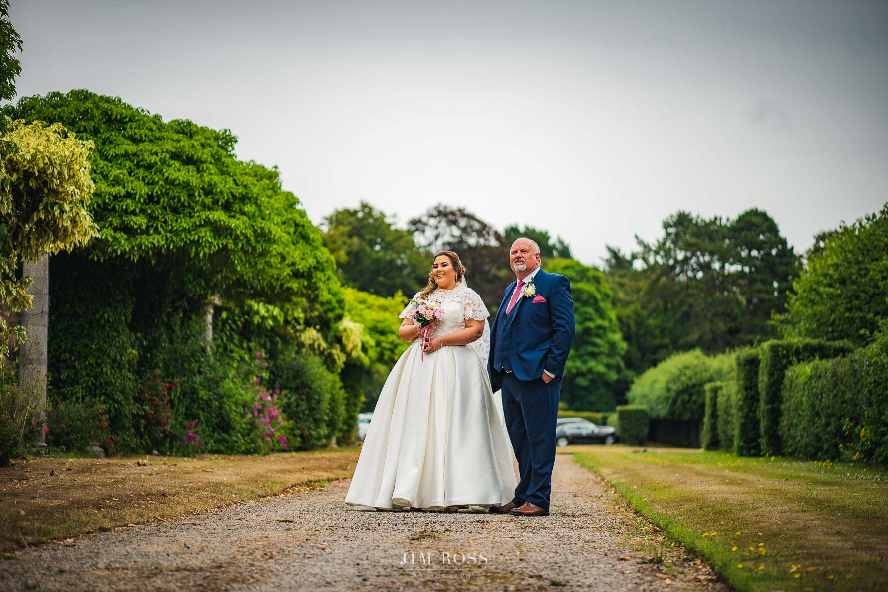 Bride and father waiting in manicured gardens
