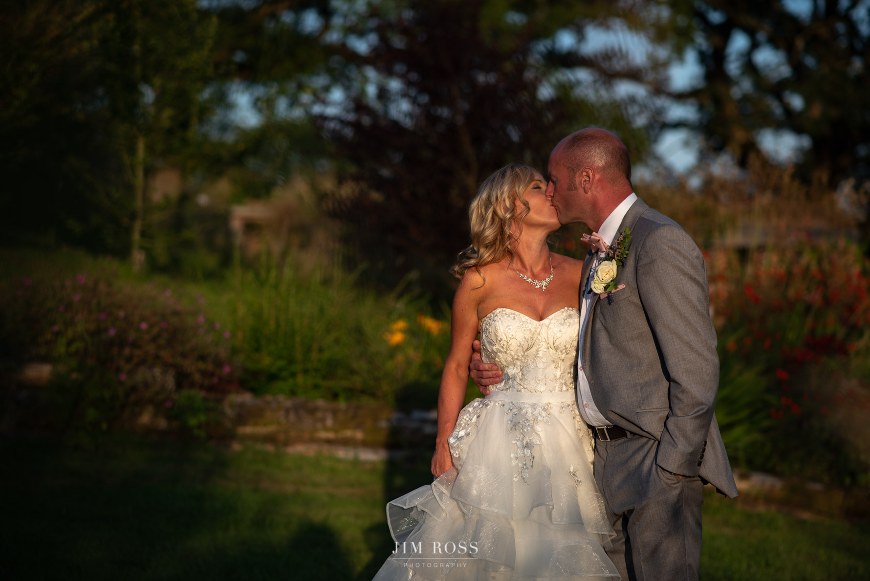 Newlyweds kiss in golden light