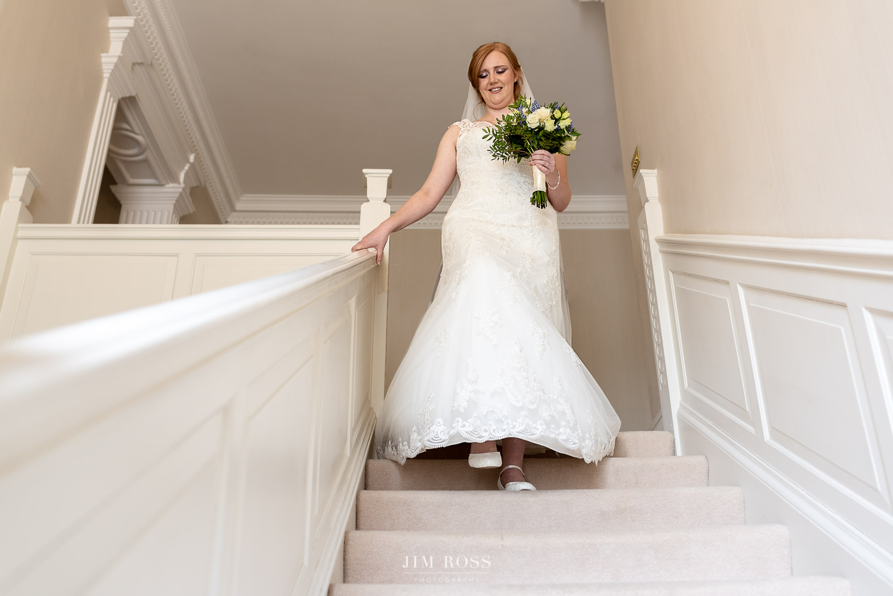 Bride walks down stairs to ceremony