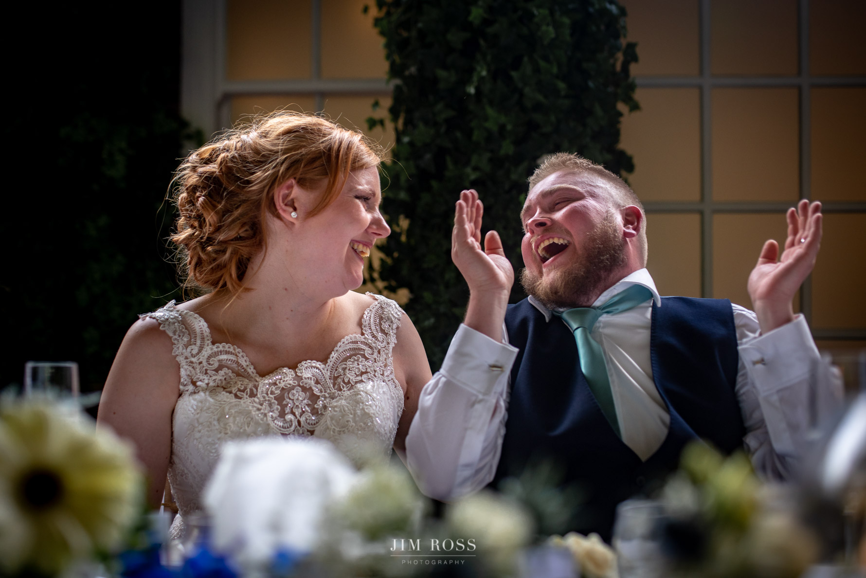 Newlyweds laughing at speeches