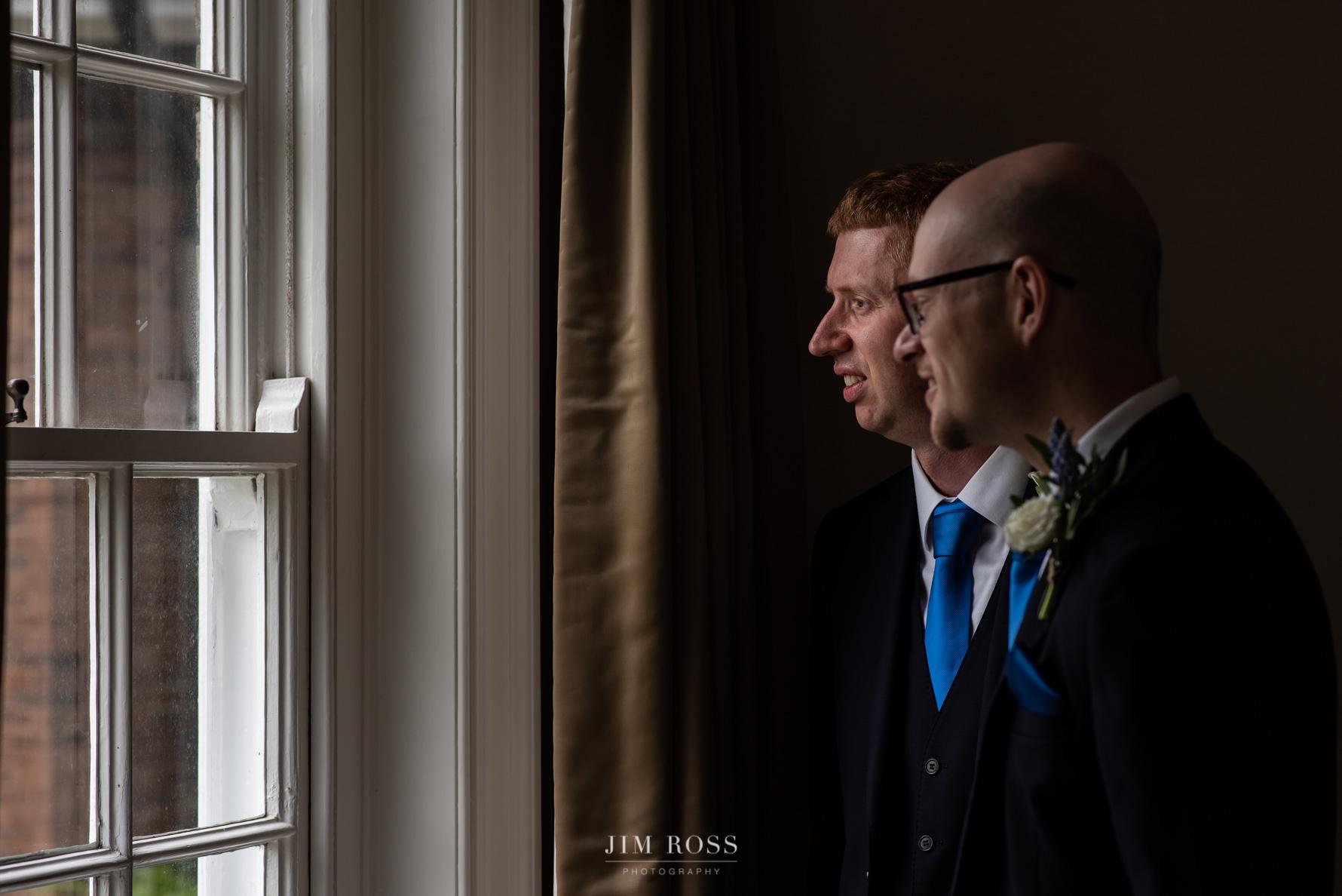 Groomsmen looking out of window
