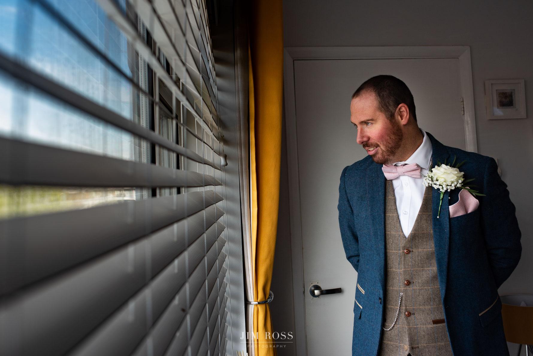 Groom looking through blinds