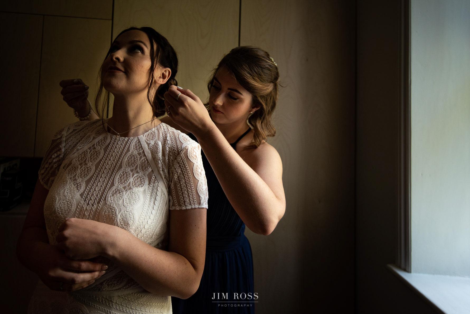 Bridesmaid helps with necklace