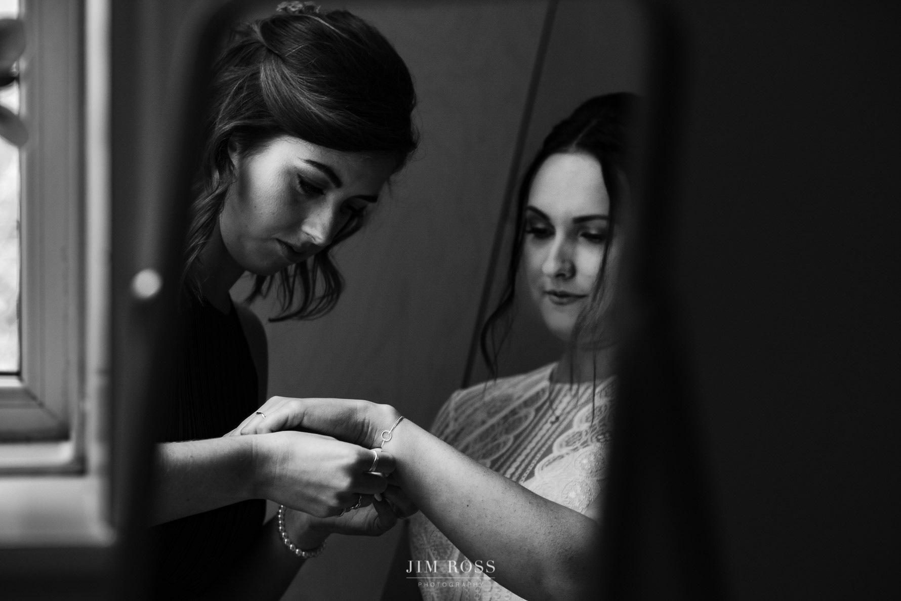 Bridesmaid helps with bracelet