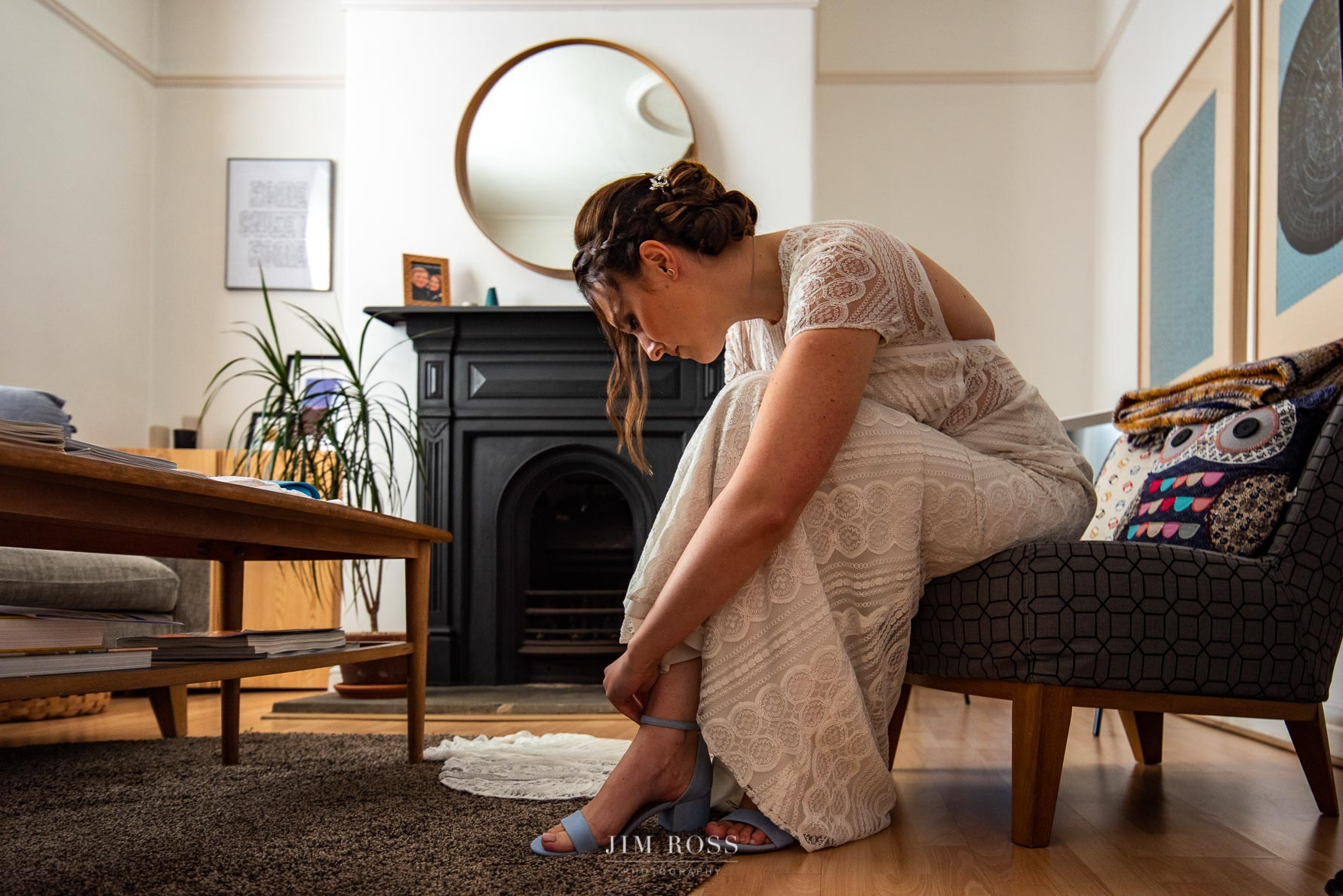 Boho bride putting on shoe