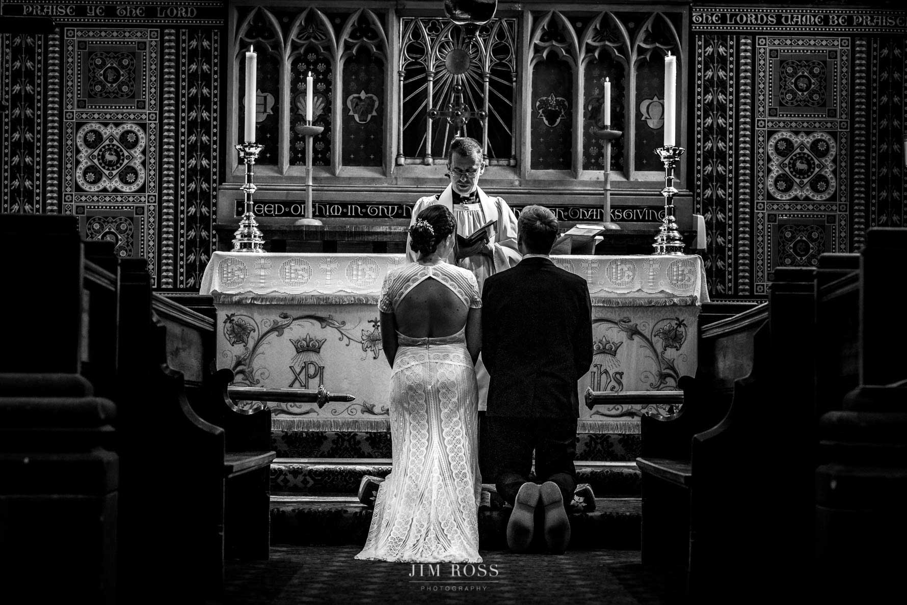 Kneeling at altar St James church Milnrow wedding